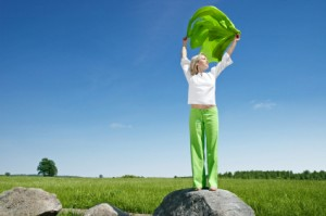 Woman standing on rock holing her arms up